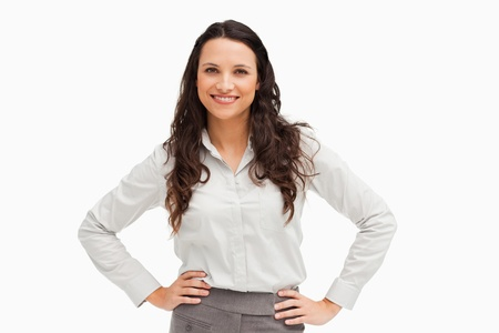 Portrait of a brunette businesswoman hands on hips smiling against a white background photo