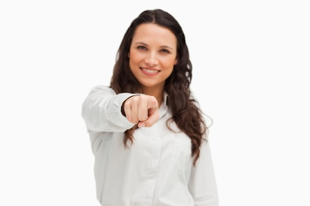 Portrait of a smiling brunette pointing against white background  photo