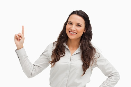 Portrait of a brunette pointing up against white background Stock Photo - 13674289