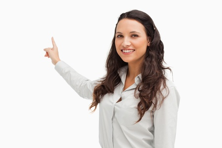 Portrait of a smiling brunette pointing in her back white background  Stock Photo - 13674354