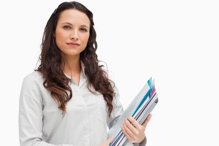 Brunette holding files against white background photo