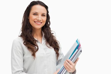 Portrait of brunette holding files against white background photo