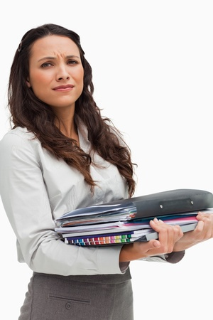 Portrait of a brunette carrying heavy files against white background photo