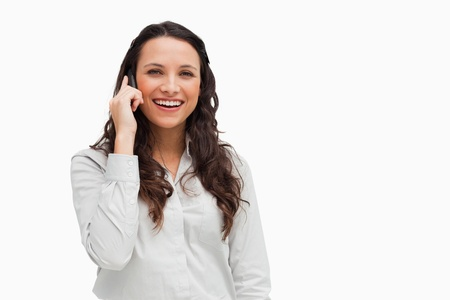 Close-up of a brunette grimacing while phoning against white background photo