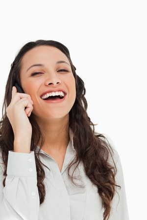 Portrait of a pretty brunette laughing while phoning against white background Stock Photo - 13672804