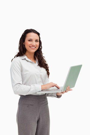 Portrait of a brunette standing while using a laptop against white background photo