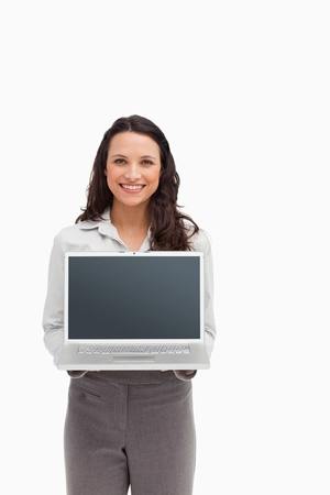 Smiling brunette standing while showing a laptop screen against white background photo