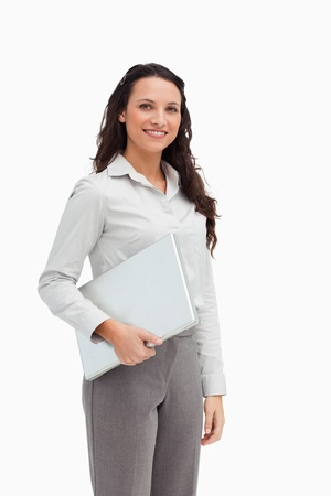 Brunette standing while holding a laptop against white background photo