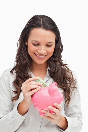 Brunette putting money in a piggy bank against white background photo