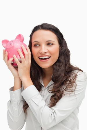 Brunette shaking a piggy bank against white background photo