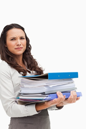 Brunette carrying a lot of files against white background photo