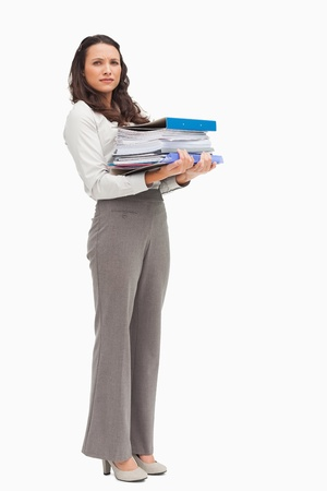 Woman carrying a lot of files against white background photo