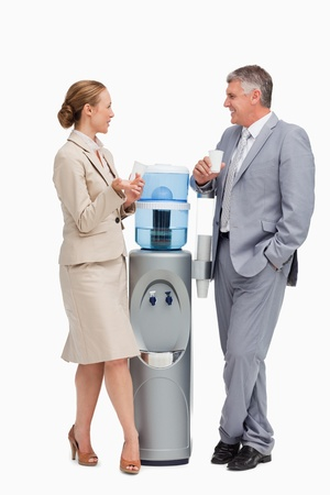 Business people talking next to the water dispenser  against white background Stock Photo - 13674259