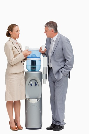 People in suit talking next to the water dispenser against white background photo