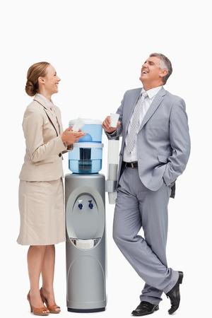 dispensador: La gente re�a al lado del dispensador de agua contra el fondo blanco