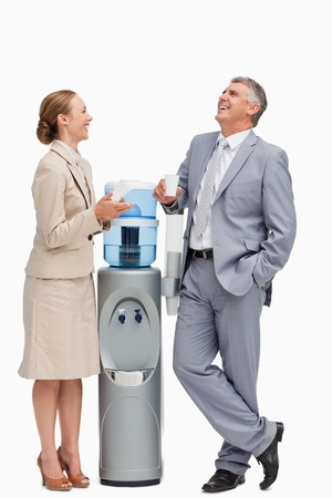People in suit laughing next to the water dispenser against white background photo