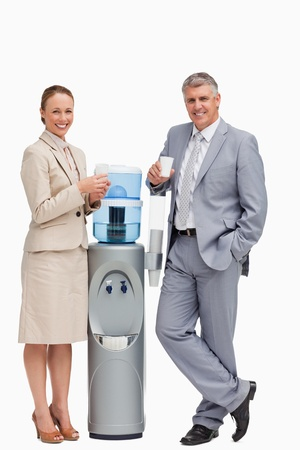 Portrait of business people smiling next to the water dispenser against white background photo