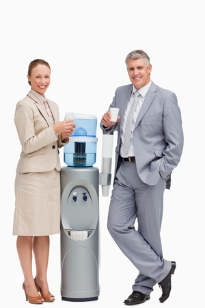 Portrait of smiling business people next to the water dispenser against white background photo