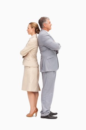 Business people with folded arms back to back against white background photo