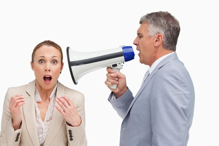 businessman using a megaphone: Businessman using a megaphone after his colleague against white background