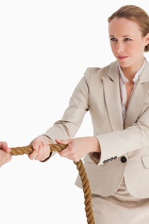 Businesswoman pulling a rope against white background photo