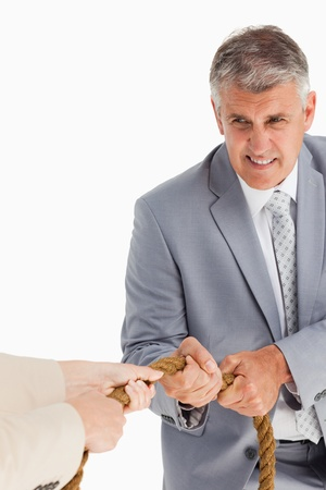 Businessman pulling the rope against white background Stock Photo