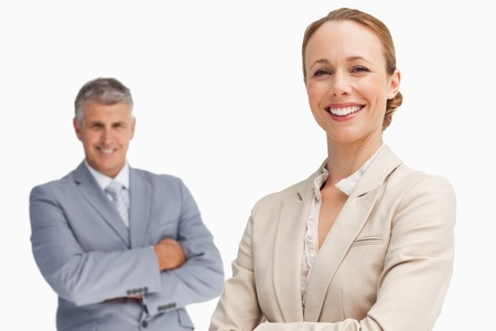 Happy business people with folded arms against white background photo