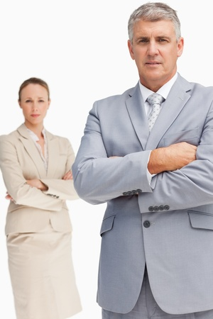 Serious business people standing with folded arms against white background photo