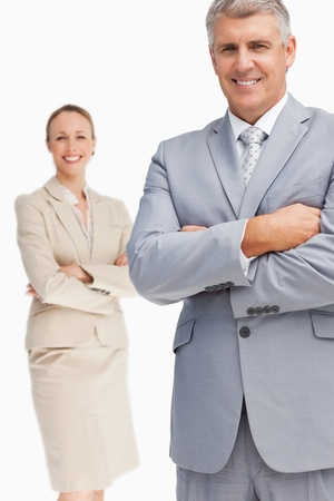 Cheerful business people with folded arms against white background photo