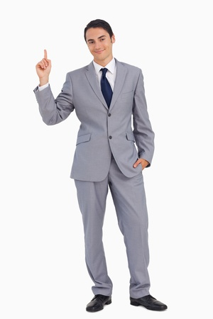 Smiling man in suit pointing up against white background photo