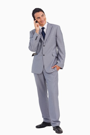 Man in a suit smiling while calling against white background photo