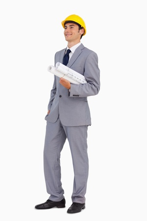 Smiling man in a suit with safety helmet and plans against white background Stock Photo - 13674579