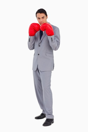 Man in a suit wearing boxing gloves againste white background photo