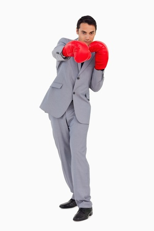 Businessman wearing red boxing gloves againste white background photo