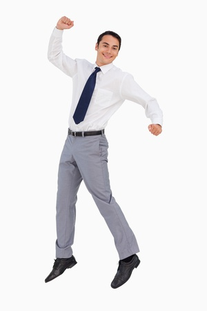 Businessman raising his arms and jumping against white background photo