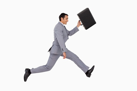 Businessman running with a suitcase against white background photo