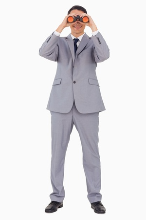 Businessman using binoculars against white background photo