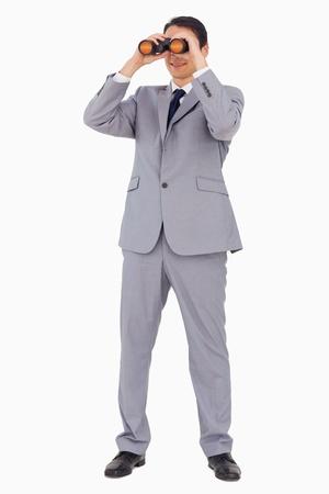 Businessman smiling while using binoculars against white background photo