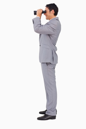 Profile of a businessman using binoculars against white background photo