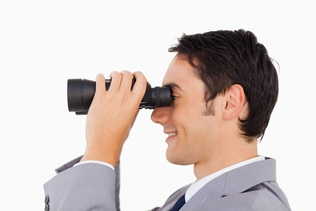 Close-up of a businessman using binoculars against white background photo