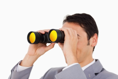 Man in a suit using binoculars against white background photo