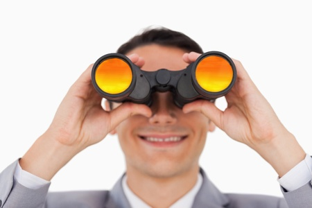 Close-up of a smiling businessman using binoculars against white background photo