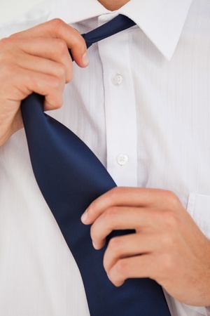 undoing: Close-up of a man undoing his tie