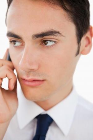 Close-up of a man in a suit calling with his cellphone against white background photo