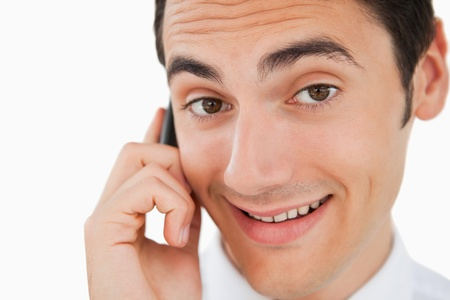 Close-up of a happy man calling with his cellphone against white background photo