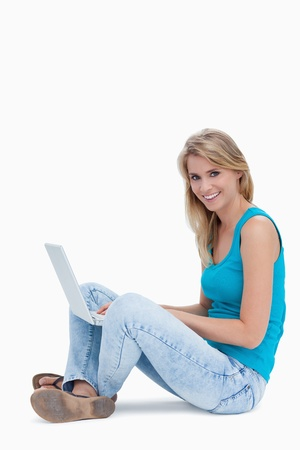 A woman is smiling at the camera with a laptop on the legs against a white background Stock Photo - 13674296