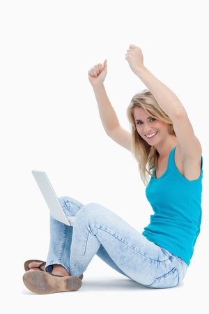 A smiling woman with her arms in the air has a laptop between her legs Stock Photo - 13674271