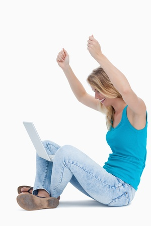 A woman with her arms in the air has a laptop between her legs Stock Photo - 13674245