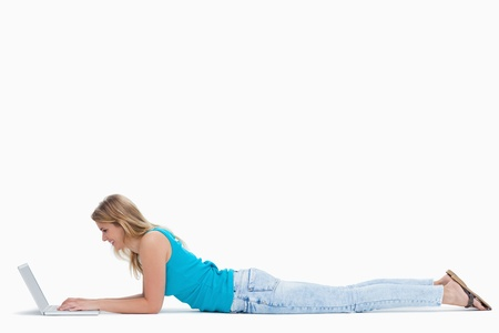 A woman is lying on the ground typing on her laptop against a white background Stock Photo - 13674927