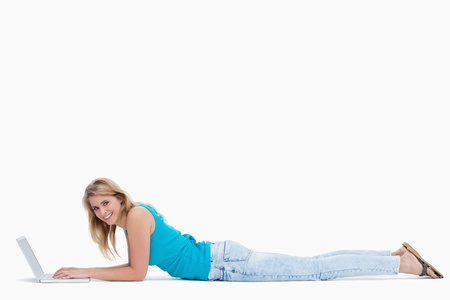 A woman smiling at the camera while lying on the gorund and typing on her laptop Stock Photo - 13674923